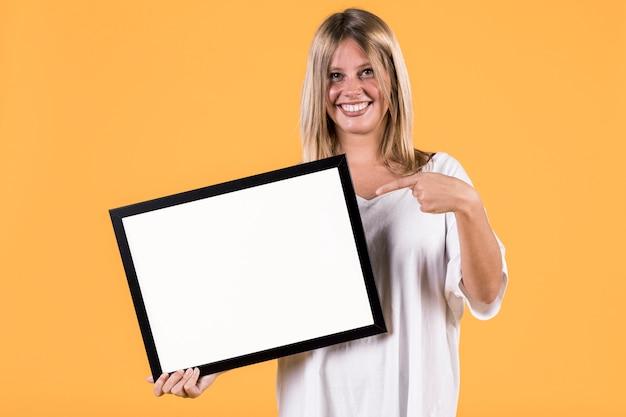 Schakel jonge blondevrouw uit die vinger op lege witte omlijsting richten Gratis Foto