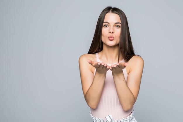 Schattig aantrekkelijk vrouwtje blaast kus, toont liefde aan vriendje of neemt afscheid op afstand, geïsoleerd over witte muur. aantrekkelijke jonge vrouw toont medeleven met iemand Gratis Foto