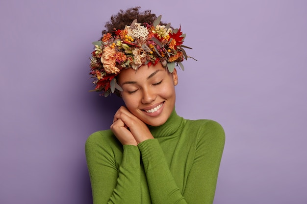 Schattig blij herfst meisje leunt naar handen gedrukt in de buurt van gezicht, kantelt hoofd, draagt een prachtige krans gemaakt van herfstplanten Gratis Foto