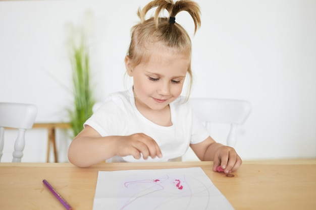 Schattig charmant meisje met paardenstaart zittend aan een bureau in de kleuterschool voor wit blad, kleuren of figuren maken met behulp van plasticine of klei, met gelukkige vreugdevolle gezichtsuitdrukking Gratis Foto