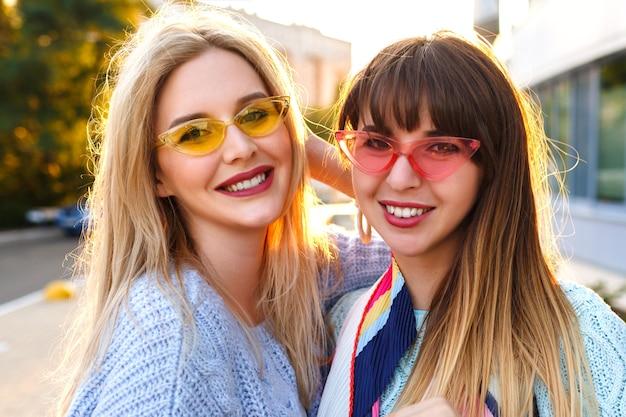 Schattig close-up zonnig portret van twee prachtige vrij elegante dames glimlachen, vintage bril en truien dragen, herfst lente tijd, vriendschap doelen. Gratis Foto