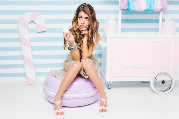 Schattig donkerharige meisje op een dieet denkt na over het eten van marshmallow zittend op een gestreepte muur. portret van aantrekkelijke jonge vrouw met smakelijke cake in hand koelen op grote stuk speelgoed makaron. Gratis Foto