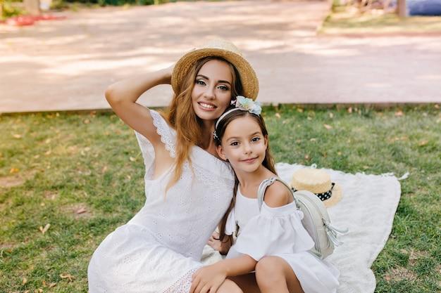 Schattig donkerogige meisje met lederen rugzak poseren op deken met stijlvolle jonge moeder draagt strooien hoed. outdoor portret van verfijnde vrouw in kanten jurk omhelst dochter met lint in haar. Gratis Foto
