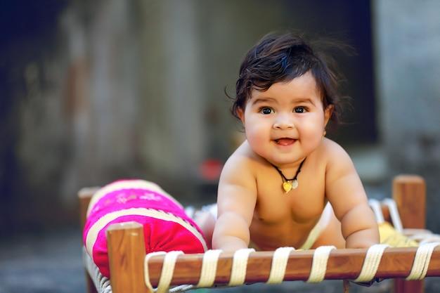 Schattig indiase klein kind glimlach en spelen op houten bed Premium Foto