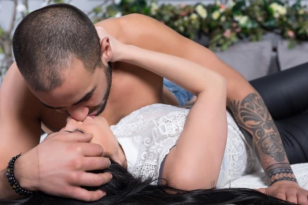 Schattig internationaal koppel man met blote borst, getatoeëerde handen en brunette vrouw zoenen liggend op het grijze gezellige bed in de slaapkamer Premium Foto