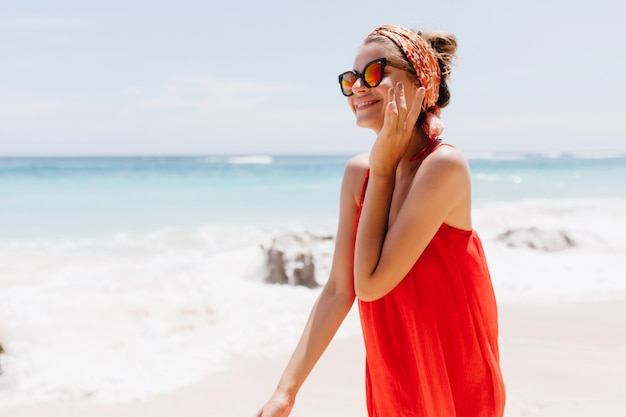 Schattig kaukasisch meisje zomer doorbrengen op exotische plek in de buurt van zee. buiten foto van sierlijke glimlachende dame in zonnebril poseren op het strand Gratis Foto