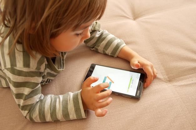 Schattig kind meisje spelen spel op slimme telefoon Premium Foto