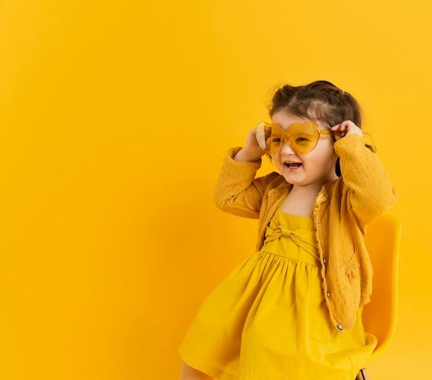 Schattig kind poseren terwijl het dragen van een zonnebril Gratis Foto