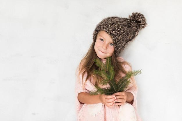 Schattig klein meisje bedrijf fir tak Gratis Foto