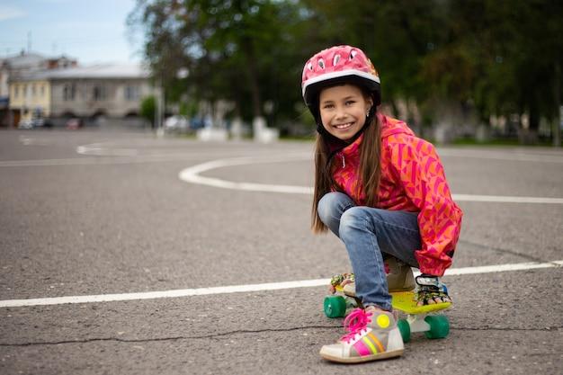 Schattig klein meisje dragen helm rijden op een skateboard in mooie zomerse park Premium Foto