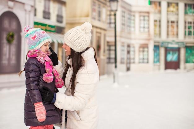 Schattig klein meisje en haar jonge moeder op een ijsbaan Premium Foto
