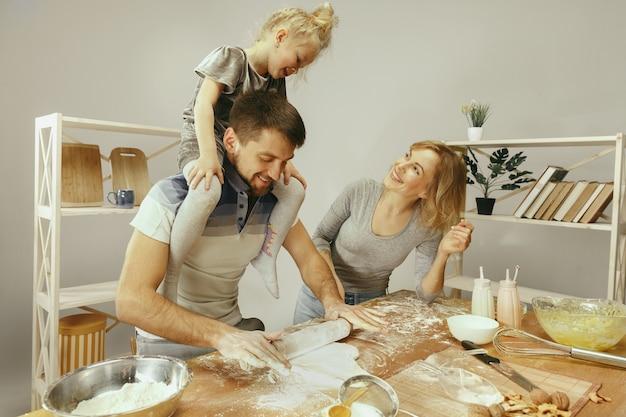 Schattig klein meisje en haar mooie ouders bereiden het deeg voor de taart in de keuken thuis. familie levensstijl concept Gratis Foto