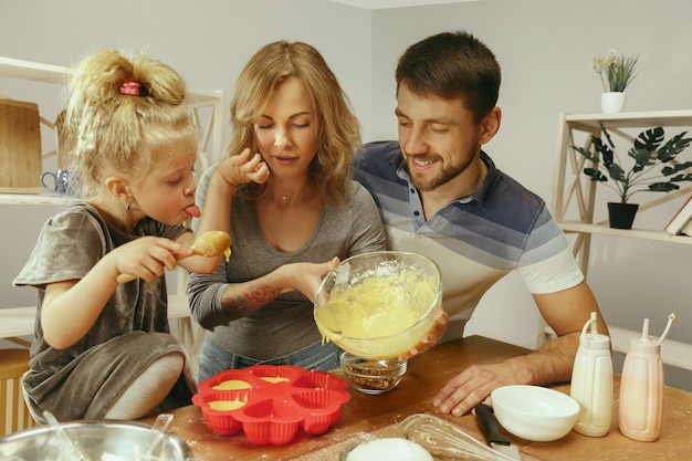 Schattig klein meisje en haar mooie ouders bereiden het deeg voor de taart in de keuken thuis Gratis Foto