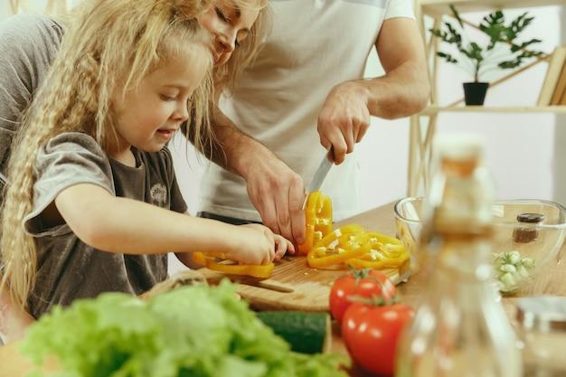 Schattig klein meisje en haar mooie ouders zijn groenten snijden en glimlachen tijdens het maken van salade in de keuken thuis. familie levensstijl concept Gratis Foto