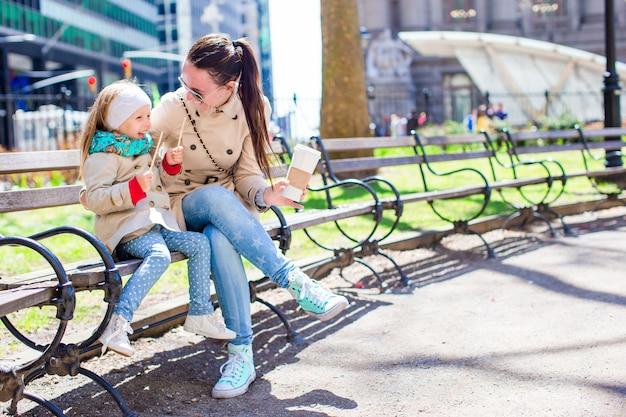 Schattig klein meisje en moeder genieten van zonnige dag op new york city Premium Foto