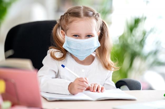 Schattig klein meisje, huiswerk, schrijven in notitieblok, met behulp van laptop, e-learning Premium Foto