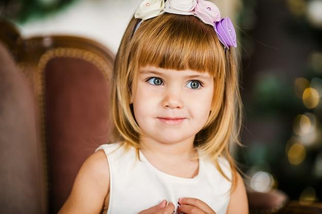 Schattig klein meisje in de witte jurk met mooie krans in de buurt van de kerstboom Premium Foto