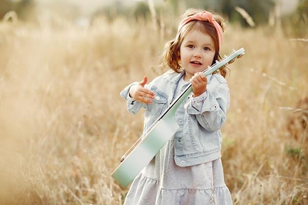 Schattig klein meisje in een park spelen op een gitaar Gratis Foto