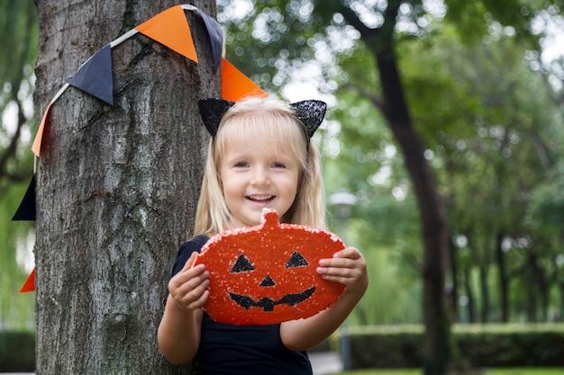 Schattig klein meisje in kostuum van zwarte kat voor halloween Premium Foto