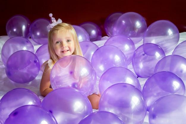 Schattig klein meisje in stijlvolle jurk viert verjaardag met paarse ballonnen Premium Foto