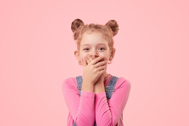 Schattig klein meisje in vrijetijdskleding die mond bedekt met handen terwijl het geheim wordt gehouden en camera met glimlach tegen roze achtergrond bekijkt Premium Foto