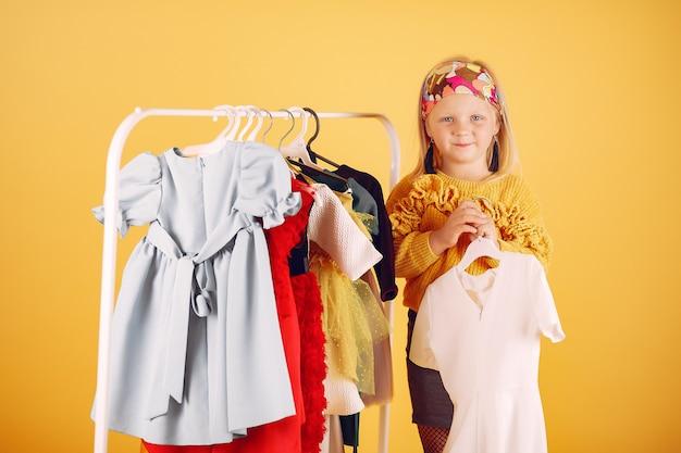 Schattig klein meisje met boodschappentassen op een gele achtergrond Gratis Foto