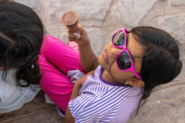 Schattig klein meisje met een zonnebril een heerlijk ijsje eten Premium Foto