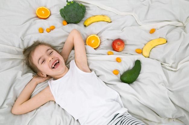 Schattig klein meisje met groenten en fruit. Gratis Foto