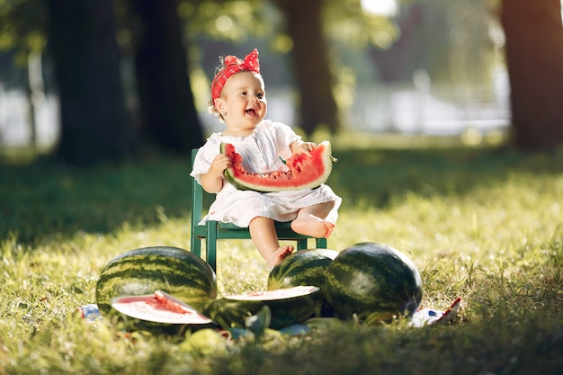 Schattig klein meisje met watermeloenen in een park Gratis Foto