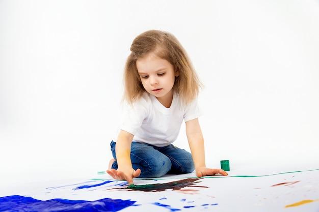 Schattig klein meisje, modern kapsel, wit shirt, spijkerbroek tekent foto's met haar handen met verf Premium Foto