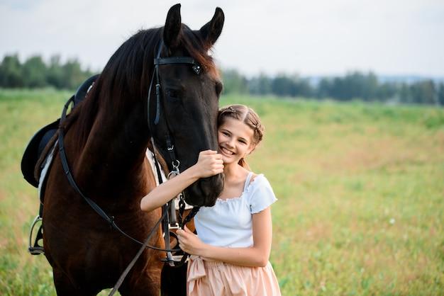 Schattig klein meisje op een paard in een zomer veld jurk. zonnige dag Premium Foto