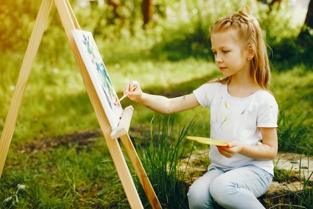 Schattig klein meisje schilderij in een park Gratis Foto