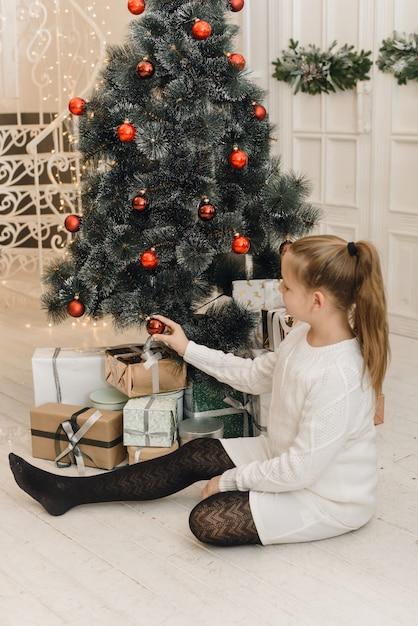 Schattig klein meisje siert de kerstboom met nieuwjaar speelgoed en rode ballen. een meisje in een witte gebreide trui en jurk zit naast geschenken en hangt ballen aan een kunstmatige spar Premium Foto