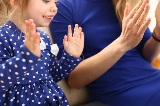 Schattig klein meisje speelt met moeder pat-a-cake Premium Foto