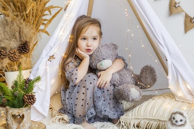 Schattig klein meisje spelen met een teddybeer in een wigwam thuis. nieuwjaars versieringen. Premium Foto