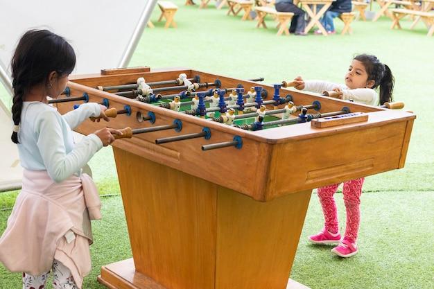 Schattig klein meisje tafelvoetbal spelen Premium Foto