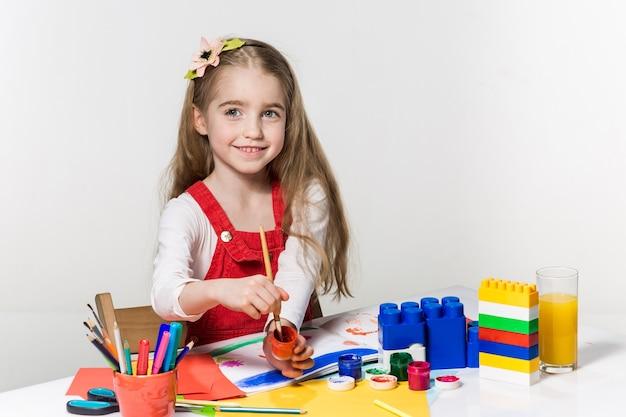 Schattig klein meisje tekenen met verf en penseel thuis Gratis Foto