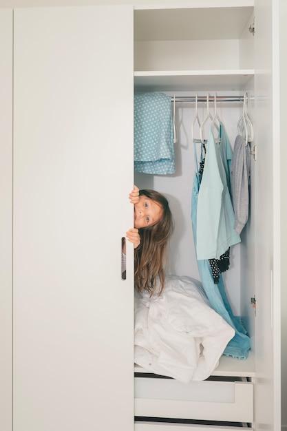 Schattig klein meisje verstopt in de kledingkast Premium Foto