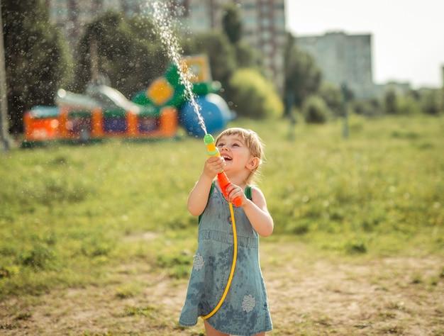 Schattig klein meisje waterpistool spelen Premium Foto