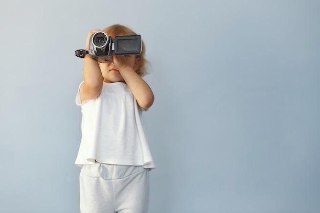 Schattig klein meisje, zittend in een studio op een blauwe achtergrond Gratis Foto