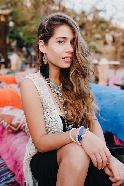 Schattig langharige meisje in trendy armbanden en oorbellen poseren buiten tijdens het rusten op het park-feest Gratis Foto