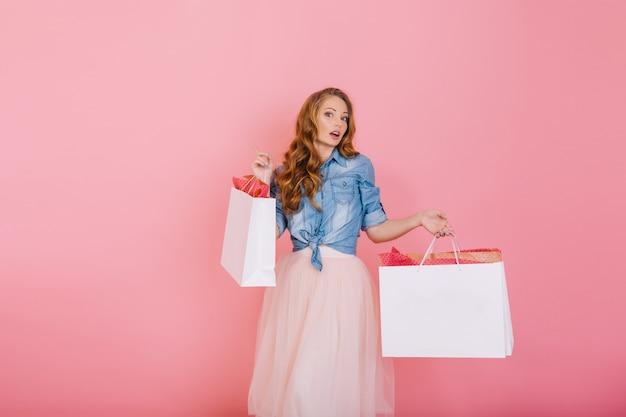 Schattig langharige stijlvolle meisje in trendy rok met papieren zakken uit boetiek met verbaasde gezichtsuitdrukking. portret van het krullende jonge vrouw stellen na het winkelen geïsoleerd op roze achtergrond Gratis Foto
