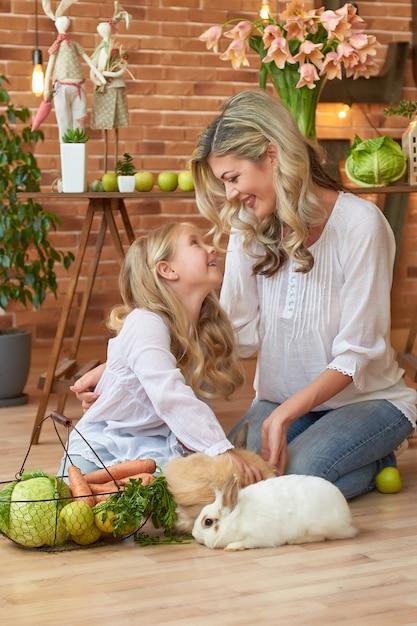 Schattig meisje en moeder spelen met konijn Premium Foto