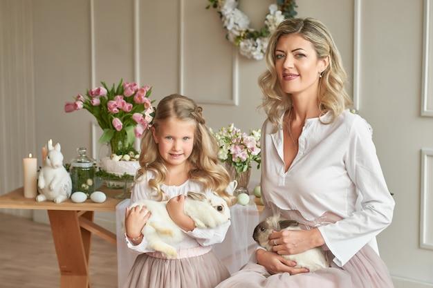 Schattig meisje en moeder spelen met konijnen Premium Foto