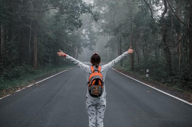 Schattig meisje hipster stijl. ga met je rug in het midden van de weg staan in de vintage stijl van de jungle. Premium Foto