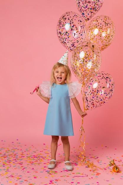 Schattig meisje in kostuum met ballonnen en feestmuts Gratis Foto
