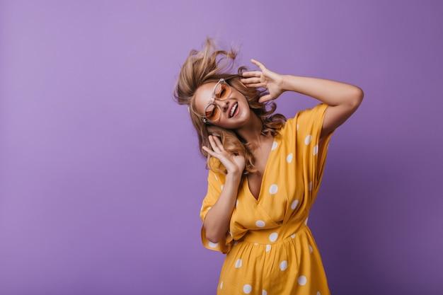 Schattig meisje in oranje kledij dansen terwijl u muziek luistert. blonde vrouw geniet van favoriete liedje. Gratis Foto