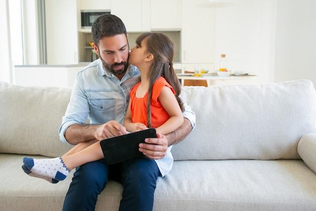 Schattig meisje kuste haar vader terwijl hij tablet gebruikt. Gratis Foto