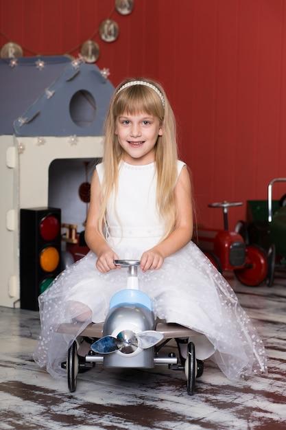 Schattig meisje speelt met speelgoedauto's. rijdt op een speelgoedmachine met typemachine. Premium Foto