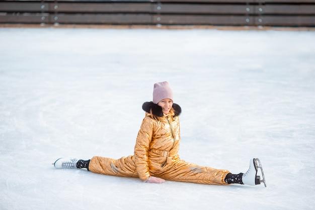 Schattig meisje zittend op ijs met schaatsen na de herfst Premium Foto